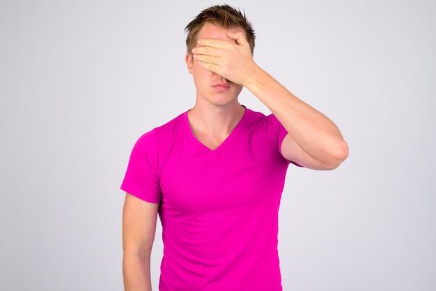 흰 벽에 보라색 셔츠를 입고 젊은 잘 생긴 남자의 초상화