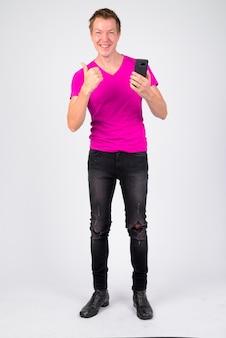 白い壁に紫色のシャツを着ている若いハンサムな男の肖像画