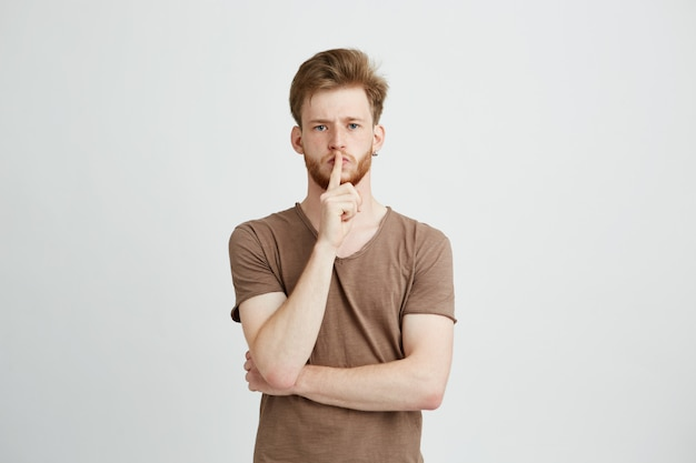 沈黙を保つためにストレートのひげを示す若いハンサムな男の肖像画。