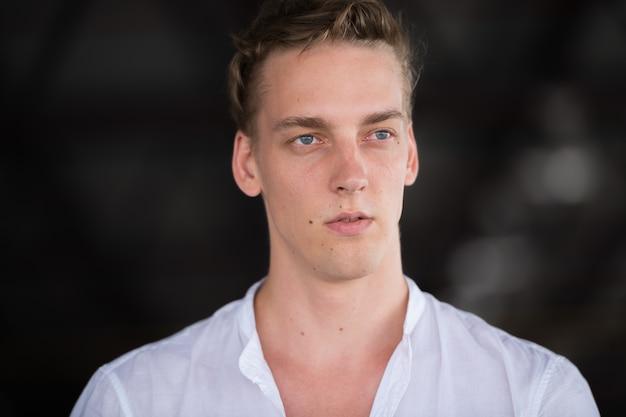 屋外で巻き毛を持つ若いハンサムな男の肖像画