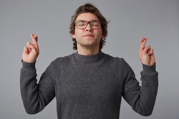 眼鏡をかけた若いハンサムな男の肖像画は灰色のセーターを着て、目を閉じて、交差した指と幸運を願って灰色の背景の上に立っています。