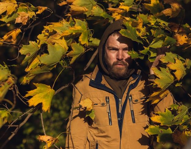 憂鬱な怒っている顔を持つ若いハンサムな男の肖像画は、カエデの森のカメラを見てください