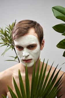 Портрет молодого красавца с белой косметической маской на лице на фоне зеленых растений. уход за лицом для мужчин