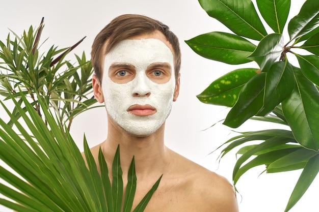 緑の植物を背景に彼の顔に白い化粧マスクを持つ若いハンサムな男の肖像画。男性のフェイスケア