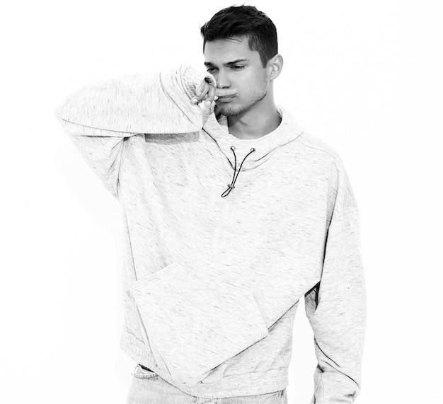 Портрет молодого красивого модельного человека одел в серой вскользь одежде с капюшоном представляя на белой стене. изолированные