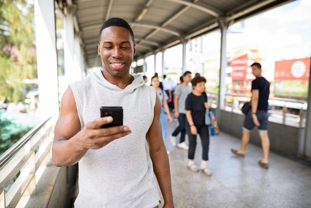 街の歩道橋でジムの準備ができて若いハンサムな筋肉のアフリカ人の肖像画