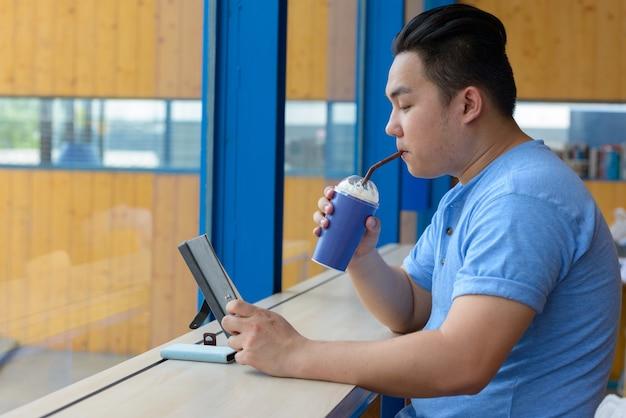 コーヒーショップでリラックスした若いハンサムな太りすぎのフィリピン人男性の肖像画