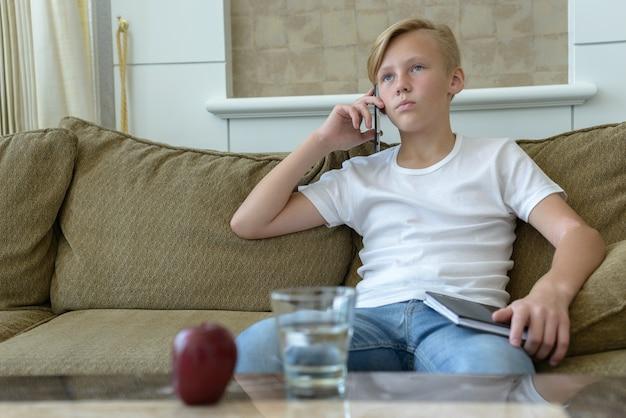 自宅のリビングルームでブロンドの髪を持つ若いハンサムなスカンジナビアの少年の肖像画