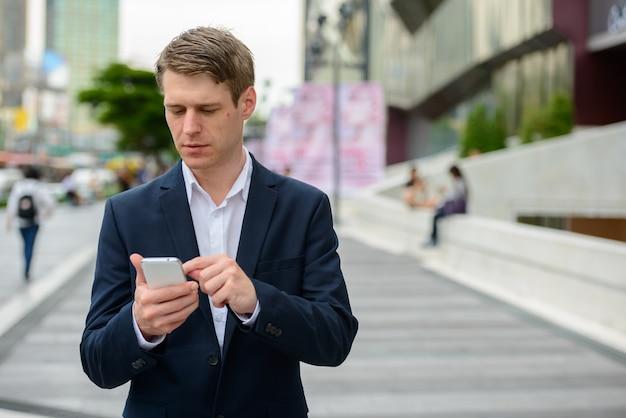 Портрет молодого красивого скандинавского бизнесмена со светлыми волосами на улицах города на открытом воздухе