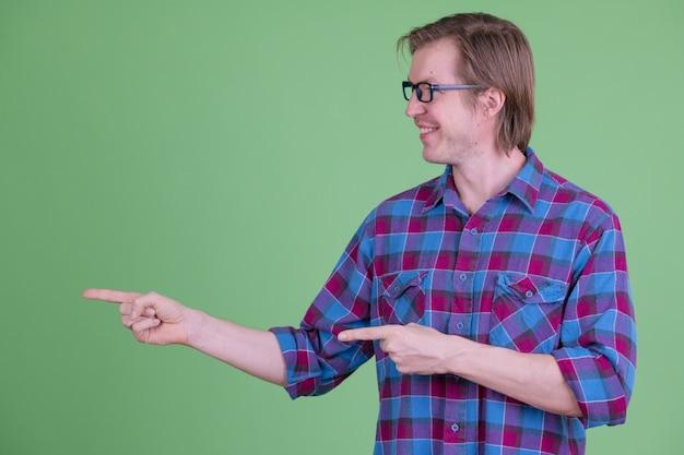クロマキーまたは緑の壁に眼鏡をかけた若いハンサムなスカンジナビアの流行に敏感な男の肖像画