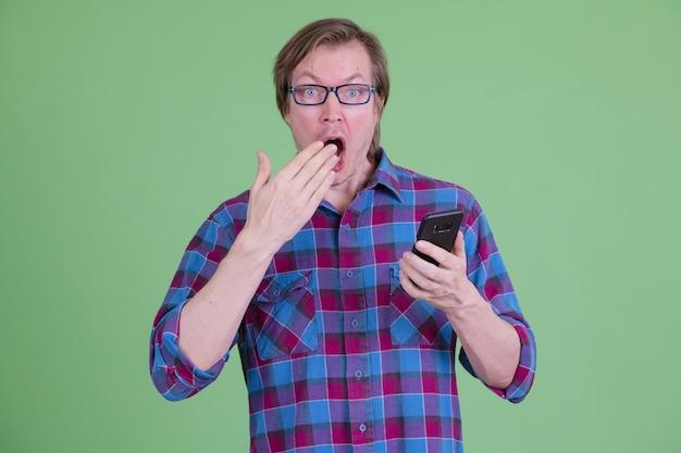 크로마 키 또는 녹색 벽에 안경을 가진 젊은 잘 생긴 스칸디나비아 힙 스터 남자의 초상화