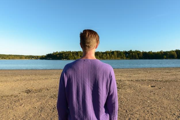 海岸の美しい風景に対する若いハンサムなスカンジナビアの男の肖像画