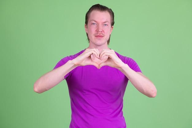 크로마 키 또는 녹색 벽에 보라색 셔츠를 입고 젊은 잘 생긴 스칸디나비아 남자의 초상화