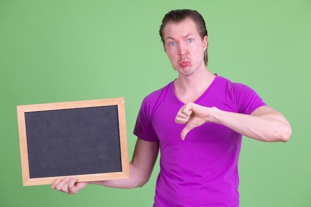 Портрет молодого красивого скандинавского мужчины в фиолетовой рубашке на фоне цветного ключа или зеленой стены
