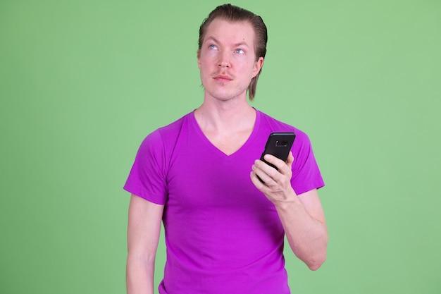 クロマキーまたは緑の壁に紫色のシャツを着ている若いハンサムなスカンジナビアの男の肖像画