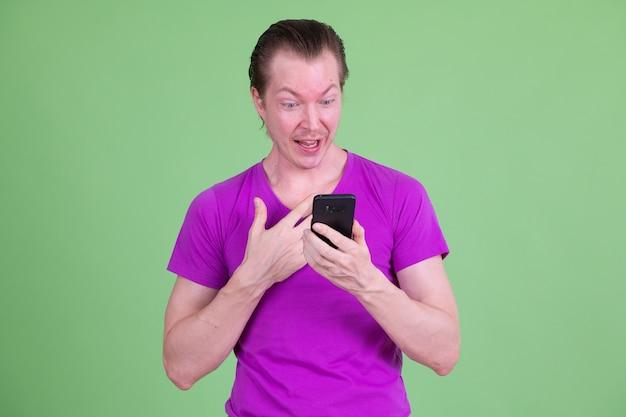 クロマキーに対して紫色のシャツを着ている若いハンサムなスカンジナビアの男の肖像画