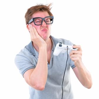 白い壁に対して隔離された眼鏡をかけている若いハンサムなスカンジナビアのオタク男の肖像画