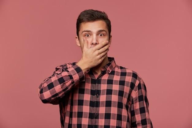 市松模様のシャツを着た若いハンサムなショックを受けた男の肖像画は、驚いた表情で目を大きく開いてカメラを見て、口を覆い、信じられないほどのニュースを聞き、ピンクの背景で隔離されます。