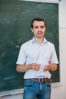 若いハンサムな学生またはクラスの空白の黒板を指して、話して、笑って先生の肖像画