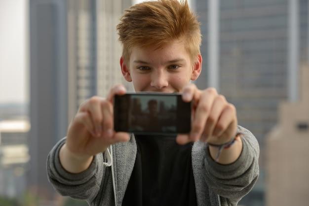 Портрет молодого красивого подростка против вида на город на открытом воздухе