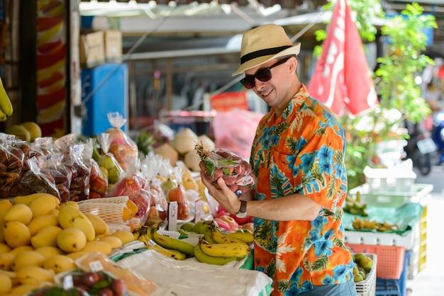 屋外のストリートマーケットで若いハンサムな観光客の男の肖像画
