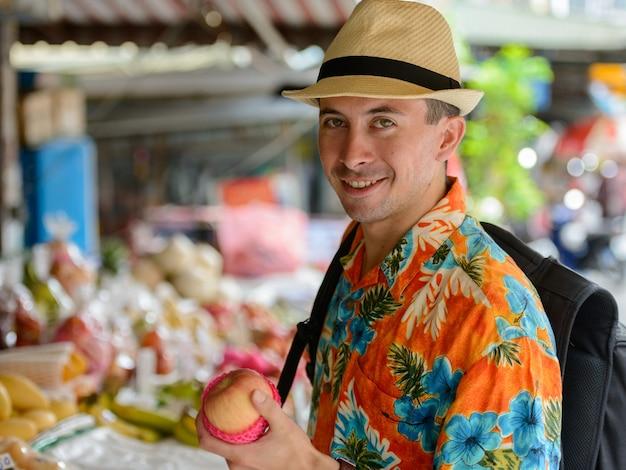 Портрет молодого красивого туриста на уличном рынке на открытом воздухе