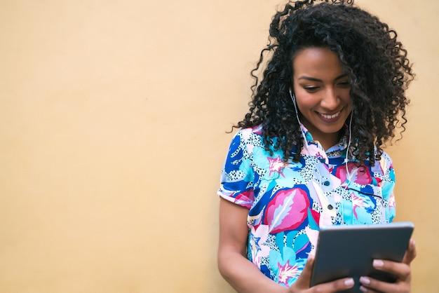 Портрет молодой счастливой афро-американской латинской женщины слушая музыку на ее цифровом планшете. концепция технологии.