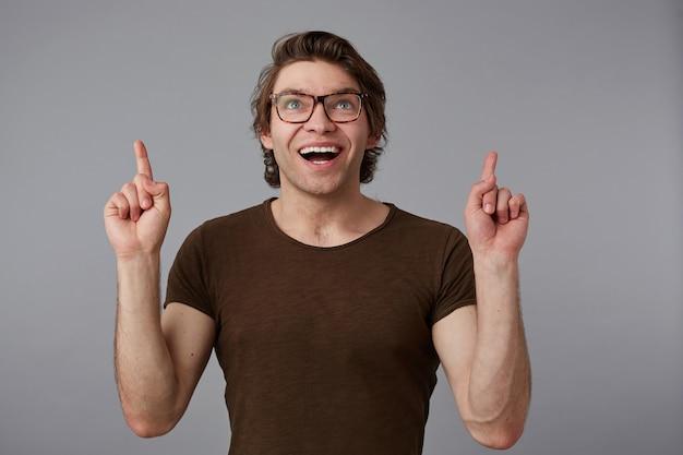Портрет молодого счастливого изумленного человека в очках, стоит на сером фоне с удивленным выражением лица, указывает пальцами на место для копирования над его головой.