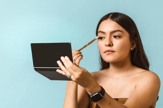 얼굴 메이크업을 적용하는 젊은 행복하고 아름다운 라틴 아메리카 여성의 초상화
