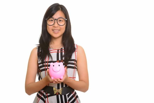 돼지 저금통을 들고 젊은 행복 한 아시아 사업가의 초상화