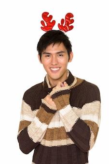 흰 벽에 고립 된 크리스마스 준비 젊은 행복 아시아 남자의 초상화
