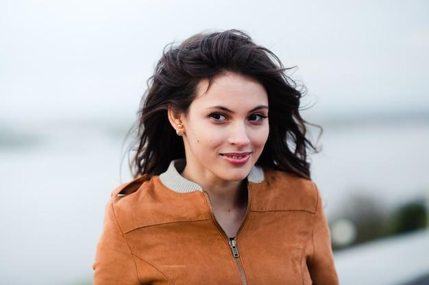 革のコートを着ている若い幸せな美しい魅力的な女性の肖像画