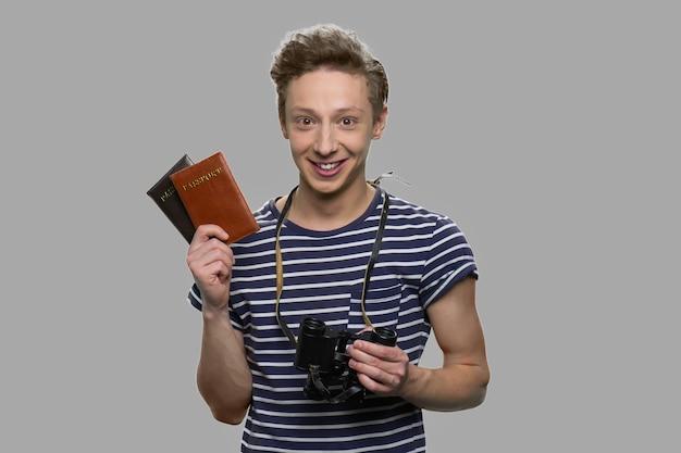 パスポートと双眼鏡を持っている若い幸せな少年の肖像画。灰色の背景にパスポートを示す観光客の男。旅行のコンセプト。