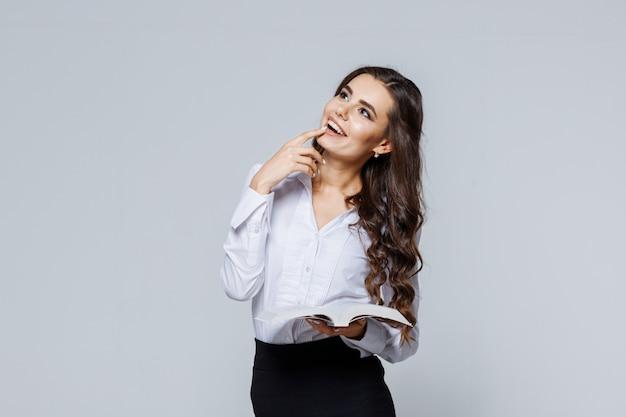 Портрет молодой счастливой бизнес-леди в классическом костюме. студентка, чтение книги.