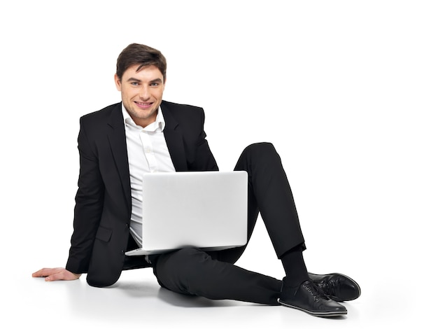 白で隔離のラップトップに取り組んでいる若い幸せなビジネスマンの肖像画。