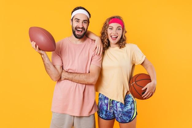고립 된 스포츠 공을 들고 머리띠를 착용 하는 젊은 행복 한 백인 피트 니스 커플의 초상화