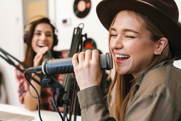 Портрет молодых счастливых кавказцев, выступающих в радиопрограмме во время записи подкаста для онлайн-шоу