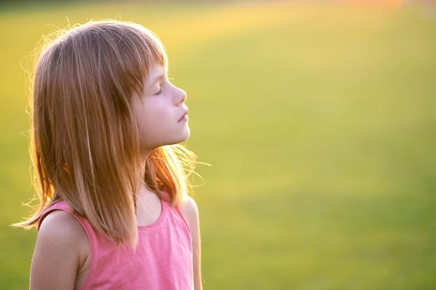 Портрет молодой счастливой детской девочки, расслабляющейся на открытом воздухе в теплый летний вечер