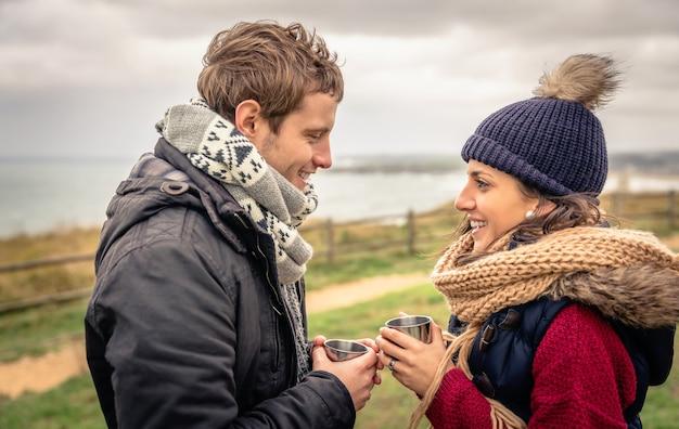 추운 날 바다와 어두운 흐린 하늘을 배경으로 뜨거운 음료를 들고 있는 젊은 행복한 커플의 초상화