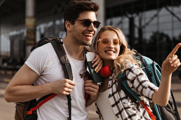 Портрет молодой счастливой вьющейся блондинки, путешествующей и позирующей в солнцезащитных очках