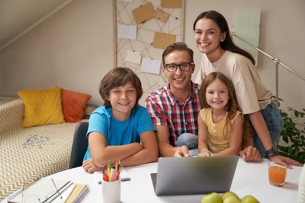 함께 숙제를 하는 동안 카메라를 보고 웃고 있는 젊은 행복한 가족의 초상화