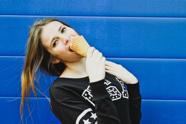 青い壁の背景の上に、屋外でアイスクリームを食べる若い幸せな女の子の肖像画