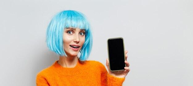 コピースペースと白い背景の上の青い髪のかつらとオレンジ色のセーターを着て、スマートフォンを手に持っている若い幸せな女の子の肖像画。パノラマバナービュー。