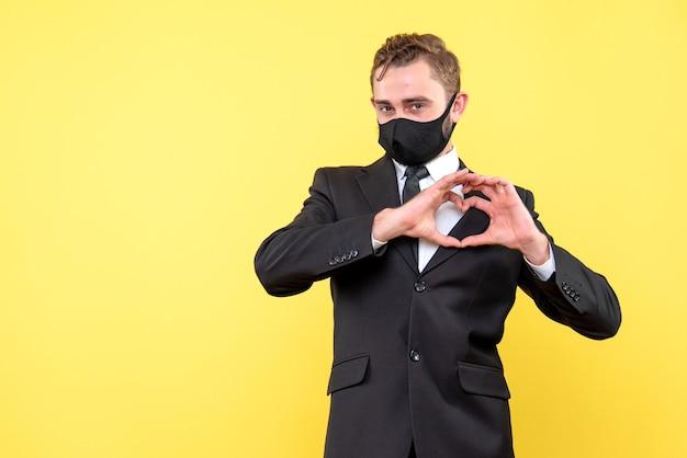 Портрет молодого счастливого парня, показывающего форму сердца с руками на желтом