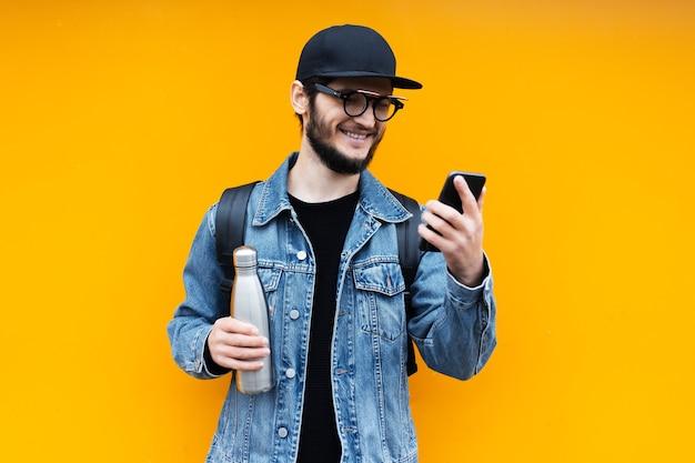 オレンジ色の若い幸せな流行に敏感な男の肖像画