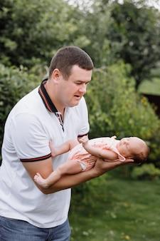 Портрет молодого счастливого человека, держащего своего новорожденного милого ребенка