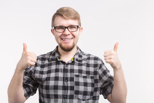 체크 무늬 셔츠를 입고 엄지 손가락으로 안경에 젊은 행복 한 남자의 초상화.