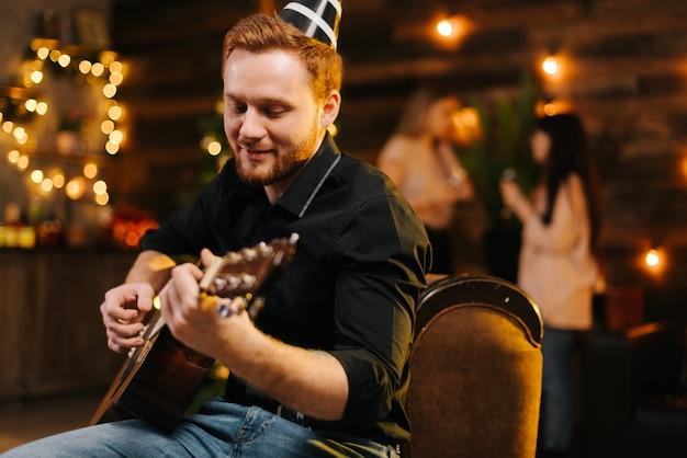 Портрет молодого счастливого человека в праздничной шляпе, играющего на гитаре на фоне говорящих друзей. рождественская елка с гирляндой и стеной с праздничным освещением в фоновом режиме.