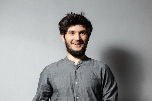 灰色の乱れた髪を持つ若い幸せな男の肖像画。