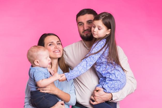 ピンクの壁の上の若い幸せな混合レース家族の肖像画。